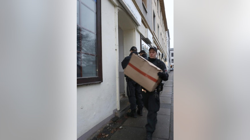 "Police officers carry cardboard boxes out of a mosque in Hamburg, northern Germany, Tuesday, Nov. 15, 2016 when hundreds of police officers search about 190 offices, mosques and apartments of members and supporters of the Islamic group ""The true religion"" in Germany after the German government announced a ban of the organization early Tuesday. (Christian Charisius/dpa  via AP)"
