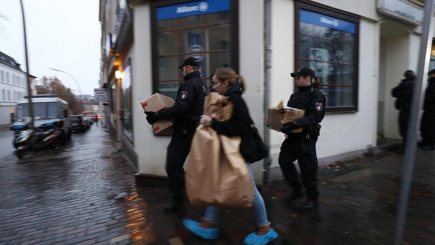 "Police carry cardboard boxes out of a mosque in Hamburg, northern Germany, Tuesday, Nov. 15, 2016 when hundreds of police officers search about 190 offices, mosques and apartments of members and supporters of the Islamic group ""The true religion"" in Germany after the German government announced a ban of the organization early Tuesday. (Christian Charisius/dpa  via AP)"
