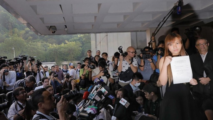 Newly elected Hong Kong lawmaker Yau Wai-ching displays jury's decision as she is surrounded by photographers and reporters outside the high court in Hong Kong Tuesday, Nov. 15, 2016. Two newly elected Hong Kong separatist lawmakers who used anti-China insults when being sworn in were disqualified from taking office in a court decision Tuesday. A Hong Kong High Court judge ruled that Sixtus Leung and Yau of the Youngspiration party violated a section of the semiautonomous Chinese city's constitution, the Basic Law, as well as laws covering oaths taken by officials. (AP Photo/Vincent Yu)