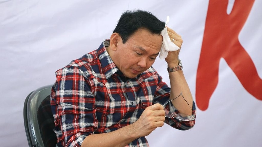 "Jakarta Governor Basuki Tjahaja Purnama, popularly known as ""Ahok,"" wipes sweat from his head during a campaign event in Jakarta, Indonesia, Wednesday, Nov. 16, 2016. Indonesian police on Wednesday named the minority Christian governor of the country's capital as a suspect in a blasphemy investigation in a major test of the Muslim-majority nation's reputation for religious tolerance. (AP Photo/Dita Alangkara)"