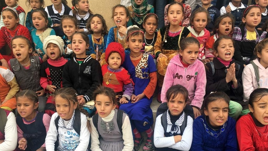 Schoolgirls gather in the Awsaja school yard after the school reopened today, in Awasaja, Iraq, Tuesday Nov. 15, 2016. For the first time in two years, children in this small village about 30 miles south of Mosul are finally going back to school. Awsaja was reclaimed by the Iraqi military just a few months ago after being under Islamic Stage control for two years. (AP Photo/Fay Abuelgasim)