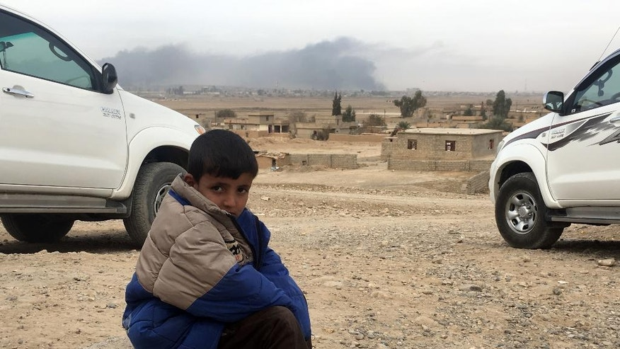 An Iraqi boy sits outside the Asawaja school as oil well fires fill the sky with plumes of black smoke, background, after the school reopened today, in Awasaja, Iraq, Tuesday Nov. 15, 2016. For the first time in two years, children in this small village about 30 miles south of Mosul are finally going back to school. Awsaja was reclaimed by the Iraqi military just a few months ago after being under Islamic Stage control for two years. (AP Photo/Fay Abuelgasim)