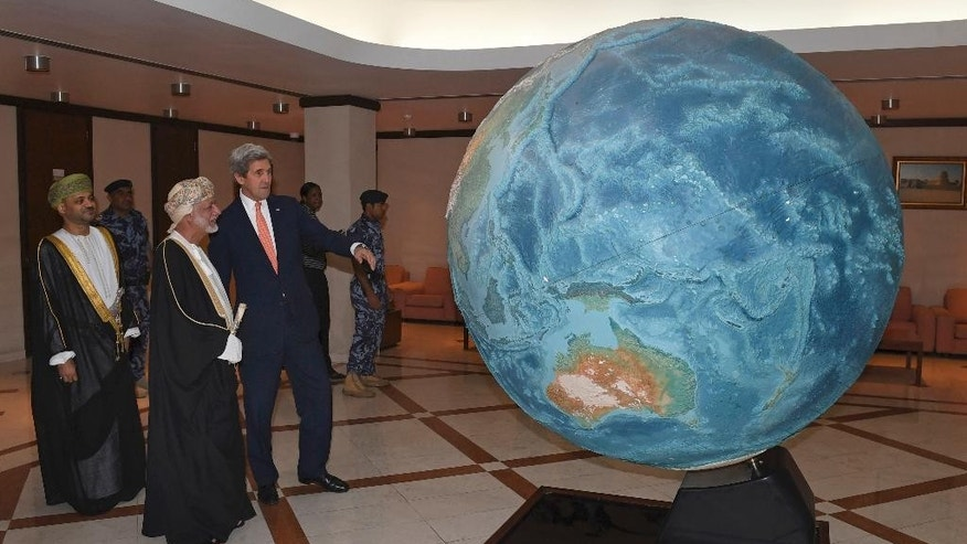 U.S. Secretary of State John Kerry, left, and the Omani Minister Responsible for Foreign Affairs, Yusuf bin Alawi bin Abdullah, look at a model of earth, in Muscat, Oman, Monday, Nov. 14, 2016. (Mark Ralston via AFP, Pool)