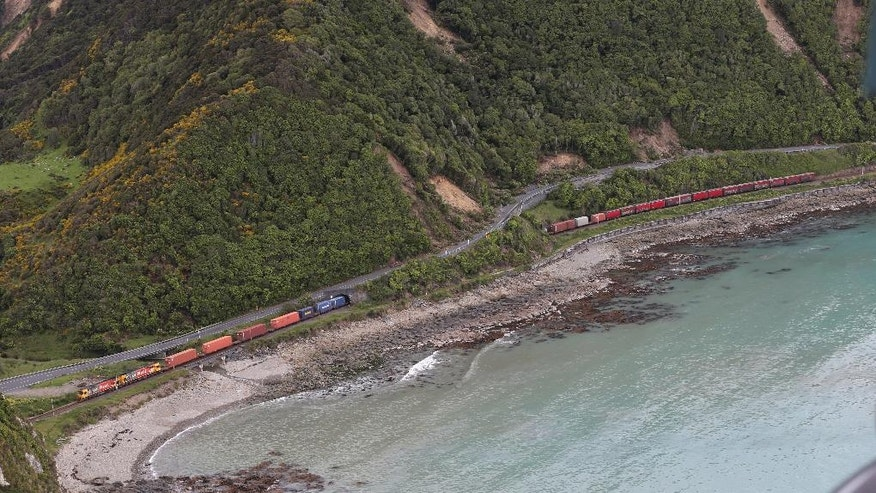 A freight train is trapped by landslides following an earthquake on the coastline, north of Kaikoura, New Zealand, Monday, Nov. 14, 2016. A powerful earthquake that rocked New Zealand on Monday triggered landslides and a small tsunami, cracked apart roads and homes and left two people dead, but largely spared the country the devastation it saw five years ago when a deadly earthquake struck the same region. (Mark Mitchell/New Zealand Herald Pool Photo via AP)
