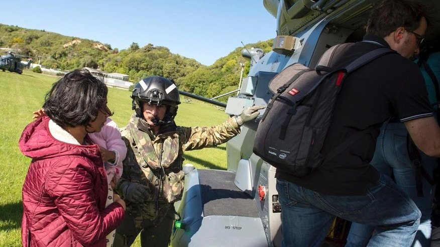 In this image provided by the Royal New Zealand Defense Force, tourists are evacuated by helicopter from Kaikoura following Monday's earthquake, in New Zealand, Tuesday, Nov. 15, 2016. New Zealand military officials said Tuesday that they had evacuated about 140 people by helicopter from a coastal town and were expecting that number to rise to 200 by the end of the day, as a major rescue operation unfolded following a powerful earthquake. (Royal New Zealand Defence Force via AP)