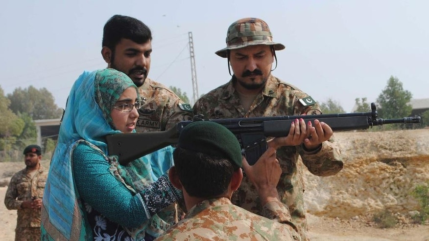 Pakistani army soldiers show a student to operate an assault rifle during their visit to a garrison in Hyderabad, Pakistan, Wednesday, Nov. 16, 2016. Pakistani Prime Minister Nawaz Sharif and the country's powerful army chief left Wednesday for a strategically located secret area bordering India to witness a military exercise of ground and air power amid increasing tension with India over Kashmir. (AP Photo/Pervez Masih)