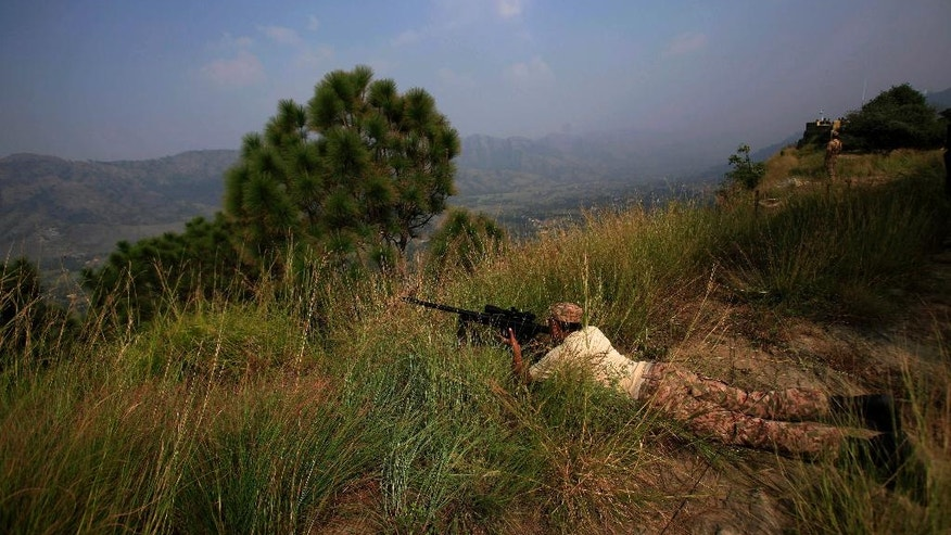 FILE - In this Oct, 1, 2016 file photo, Pakistan army soldiers take position at a forward area Bagsar post on the Line of Control (LOC), that divides Kashmir between Pakistan and India, in Bhimber, some 103 miles, 166 km, from Islamabad, Pakistan. On Monday, Nov. 14, 2016, Pakistan's army claimed that Indian troops opened fire across the LOC in the disputed Himalayan region of Kashmir, killing at least 7 soldiers. India and Pakistan have fought two of their three wars over control of Kashmir, which is divided between the two countries and claimed in its entirety by both. (AP Photo/Anjum Naveed)