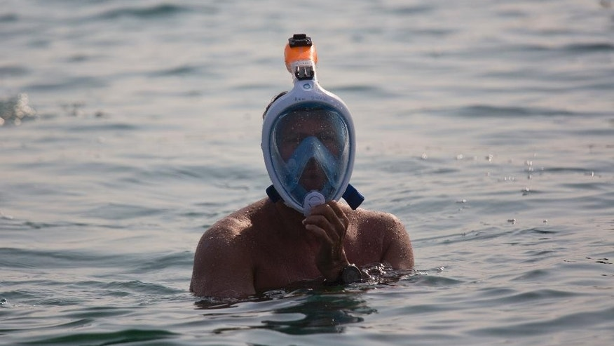 A Swimmer rests for a moment as he swims in the salty waters of the Dead Sea, from Jordan to Israel, arriving at Ein Gedi, Israel, Tuesday, Nov. 15, 2016. Swimmers from around the world plunged into the salty waters of the Dead Sea on Tuesday to attempt a seven-hour swim across the fabled lake in a bid to draw attention to its environmental degradation. Wearing protective masks and snorkels, 25 swimmers paddled through the muddy water to attempt the 9-mile (15-kilometer) swim from Jordan to Israel. (AP Photo/Ariel Schalit)