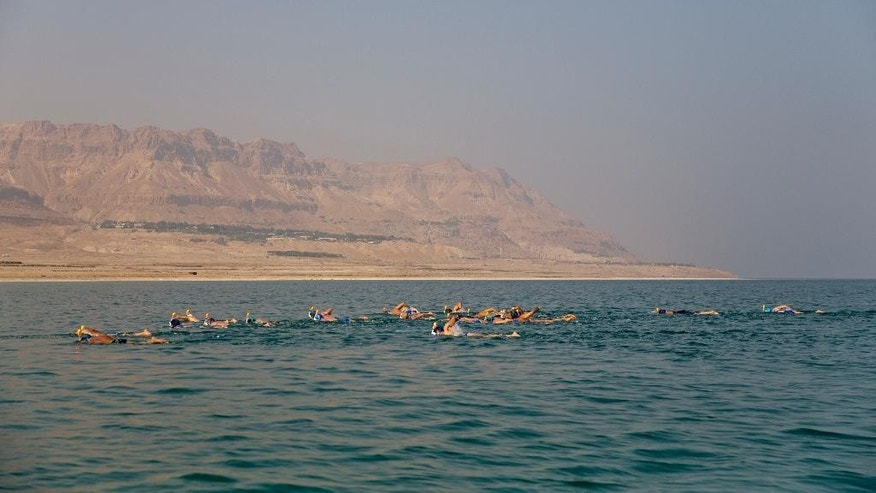 People swim in the salty waters of the Dead Sea, from Jordan to Israel, arriving at Ein Gedi, Israel, Tuesday, Nov. 15, 2016. Swimmers from around the world plunged into the salty waters of the Dead Sea on Tuesday to attempt a seven-hour swim across the fabled lake in a bid to draw attention to its environmental degradation. Wearing protective masks and snorkels, 25 swimmers paddled through the muddy water to attempt the 9-mile (15-kilometer) swim from Jordan to Israel. (AP Photo/Ariel Schalit)