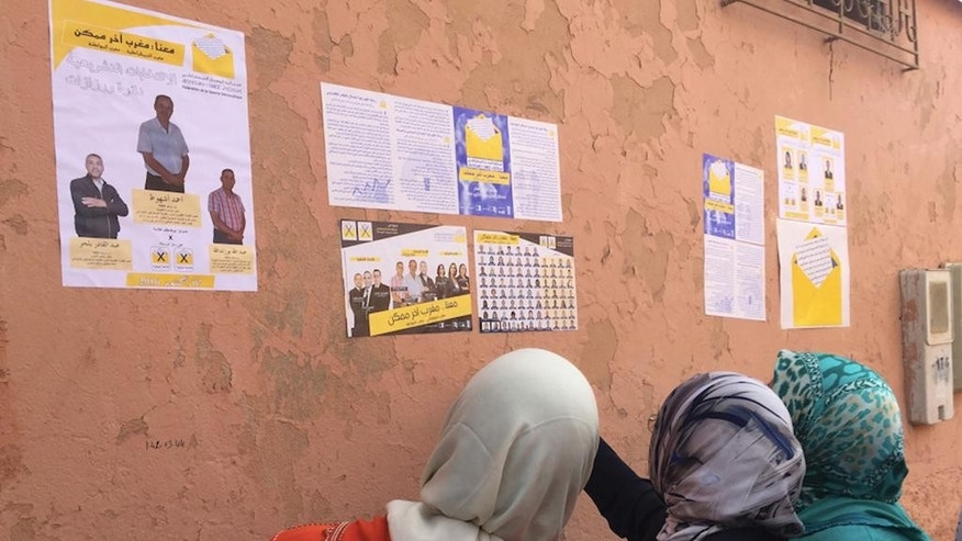 In this photo taken Tuesday, Sept. 27, 2016 in Ouarzazate, Morocco, women look at campaign posters of the Federation of the Democratic Left, lead by Nabila Mounib. Mounib campaigned across Morocco ahead of Oct. 7 parliament elections. Mounib is the country's most high-profile female politician and is seen as a trailblazer in a region where men still dominate politics. (AP Photo/Samia Errazzouki)