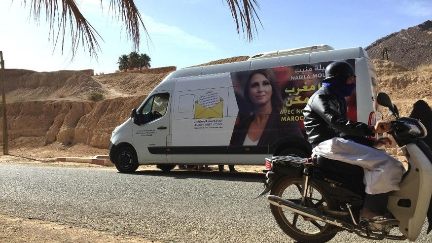 In this photo taken Monday, Sept. 26, 2016, a Moroccan man on a motorcycle drives past the campaign bus of Moroccan politician Nabila Mounib on a road between the southern towns of Guelmim and Akka, Morocco. Mounib, leader of the Federation of the Democratic Left, campaigned across Morocco ahead of Oct. 7 parliament elections. Mounib is the country's most high-profile female politician and is seen as a trailblazer in a region where men still dominate politics. (AP Photo/Karin Laub)