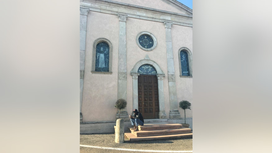 A migrant from Mali sits on the steps of a church Tuesday, Nov. 15, 2016, in the hilltop village of Fitta, under the administration of the winemaking town of Soave, Northern Italy, where residents are protesting plans to house another 100 migrants in a hotel in the industrial zone. (AP Photo/Paolo Santalucia)