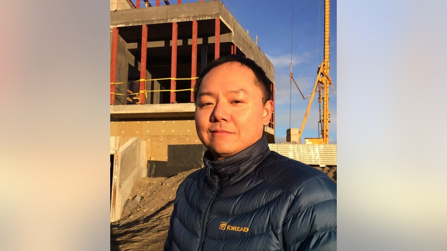 In this Monday, Oct. 31, 2016 photo, Zejun Hu, scientist at the Polar Research Institute of China, stands outside the construction site of the Aurora Observatory, a research facility to study the Northern Lights, in Karholl, northern Iceland. Construction workers are building a research facility to study the Northern Lights, whose spectacular streaks of color light up Iceland's winter skies. Funded by China's Polar Research Institute, the facility will house Chinese, Icelandic and international scientists when it opens next year. (AP Photo/Dorothee Thiesing)