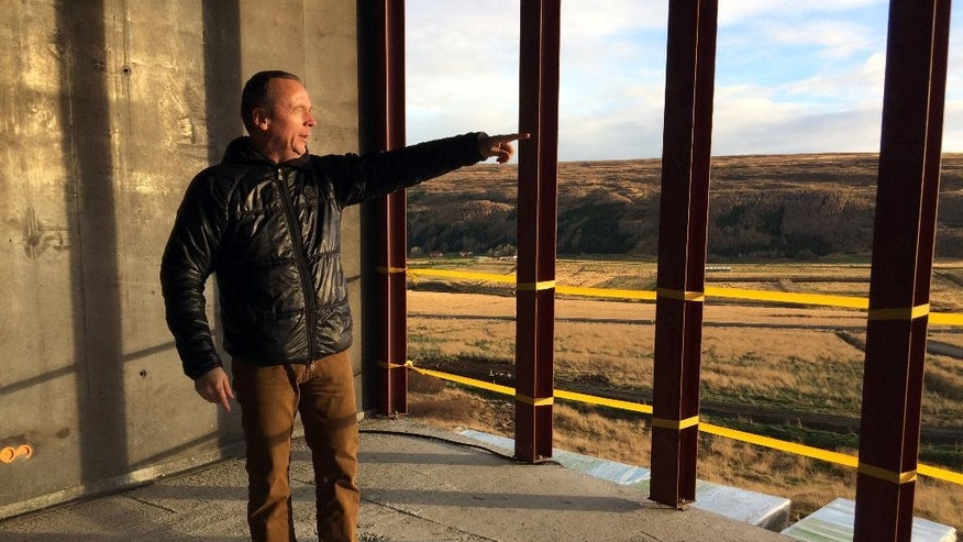 In this photo taken on Oct. 31, 2016, Reinhard Reynisson, managing director of Northeast Iceland Development Agency, looks towards a northern Iceland valley from the first floor of the construction site of Aurora Observatory, in Karholl, Iceland. Construction workers are building a research facility to study the Northern Lights, whose spectacular streaks of color light up Iceland's winter skies. Funded by China's Polar Research Institute, the facility will house Chinese, Icelandic and international scientists when it opens next year. (AP Photo/Dorothee Thiesing)
