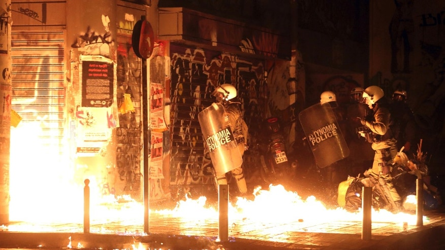 Nov. 15, 2016: Police officers walk past flames from a fire bomb thrown by demonstrators during a protest against the visit of US President Barack Obama in Athens.