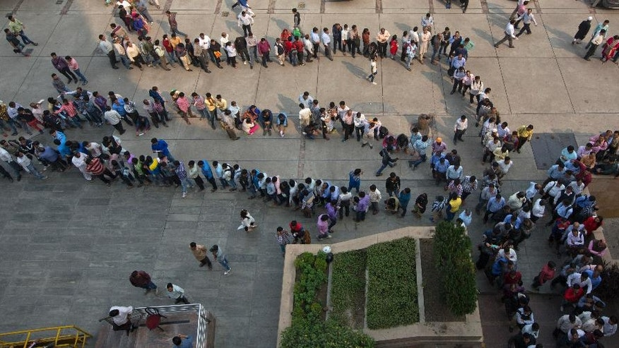 FILE- In this Nov. 15, 2016 file photo, Indians stand in queues to exchange or deposit discontinued currency notes outside an Axis Bank branch in central New Delhi, India. This is just one bank, in one city, in a country of 1.3 billion people, millions of them increasingly desperate for cash amid a chaotic government effort to crack down on corruption by banning high-denomination currency notes.  Last week, Prime Minister Narendra Modi abruptly announced in a nighttime TV address that all 500- and 1,000-rupee notes, worth about $7.50 and $15, would be withrawn immediately from circulation, a move designed to fight corruption and target people who have acquired immense hoards of cash to avoid paying taxes. (AP Photo/Manish Swarup, File)