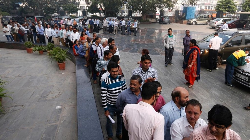 FILE- In this Nov. 11, 2016 file photo, a large queue of people wait to exchange discontinued currency outside an Axis Bank branch in central New Delhi, India. This is just one bank, in one city, in a country of 1.3 billion people, millions of them increasingly desperate for cash amid a chaotic government effort to crack down on corruption by banning high-denomination currency notes.  Last week, Prime Minister Narendra Modi abruptly announced in a nighttime TV address that all 500- and 1,000-rupee notes, worth about $7.50 and $15, would be withrawn immediately from circulation, a move designed to fight corruption and target people who have acquired immense hoards of cash to avoid paying taxes. (AP Photo/Saurabh Das, File)