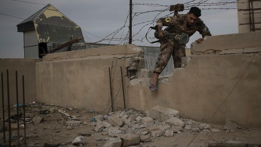 An Iraqi special forces fighter moves between buildings near the front line during fighting with Islamic State militants, in eastern Mosul, Iraq, Tuesday, Nov. 15, 2016. (AP Photo/Felipe Dana)