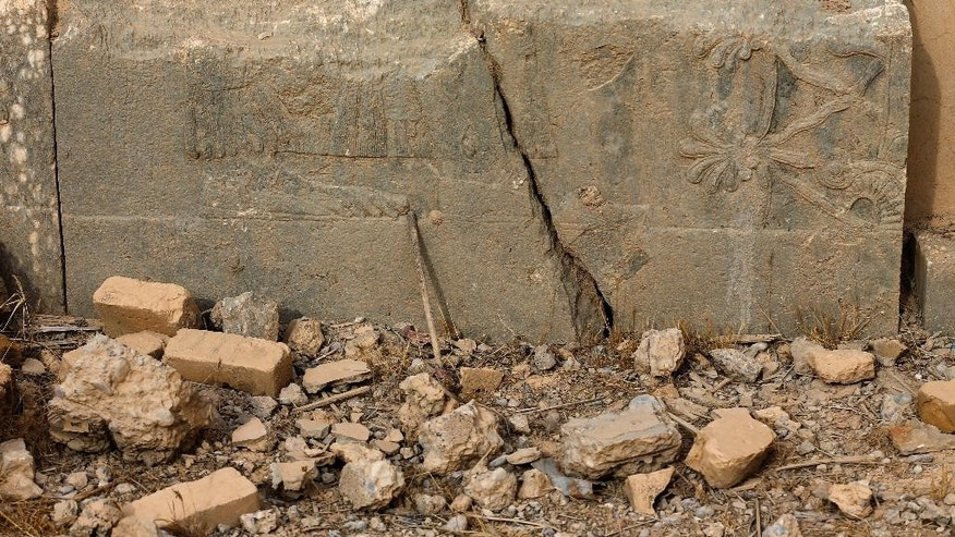 A part of carved stone slabs which were destroyed by the Islamic State militants, is seen at the ancient site of Nimrud some 19 miles (30 kilometers) southeast of Mosul, Iraq, Wednesday, Nov. 16, 2016. The late 1980s discovery of treasures in Nimrud's royal tombs was one of the 20th century's most significant archaeological finds. The government said the IS militants, who captured the site in June 2014, destroyed it the following year, using heavy military vehicles. (AP Photo/Hussein Malla)