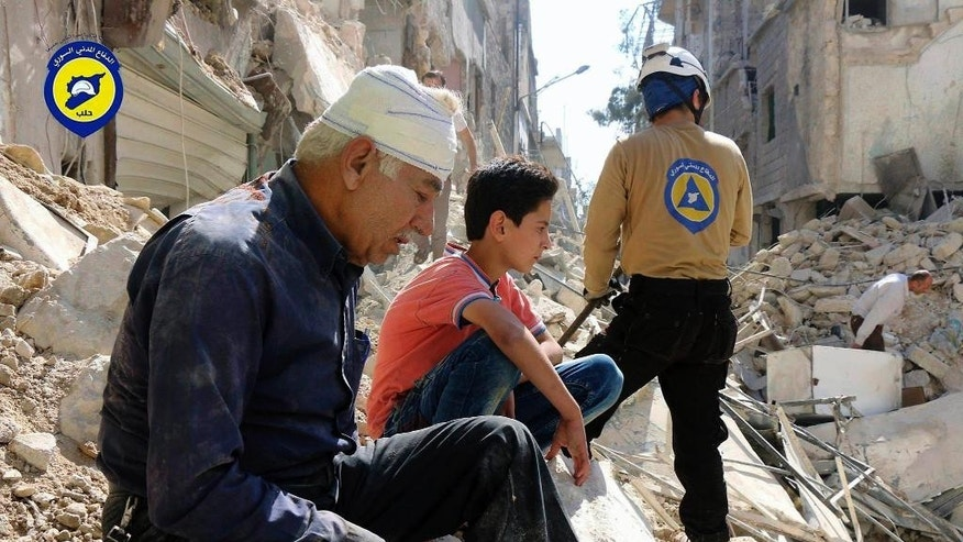 FILE -- In this Oct. 11, 2016 file photo, provided by the Syrian Civil Defense group known as the White Helmets, residents sit amongst rubble in rebel-held eastern Aleppo, Syria. Syrian opposition activists say airstrikes have hit rebel-held eastern Aleppo on Tuesday, Nov. 15, 2016, for the first time in three weeks, fearing it could signal the start of a new government offensive in the northern city. The Britain-based Syrian Observatory for Human Rights says that airstrikes struck three neighborhoods. It had no immediate word on casualties. (Syrian Civil Defense- White Helmets via AP, File)