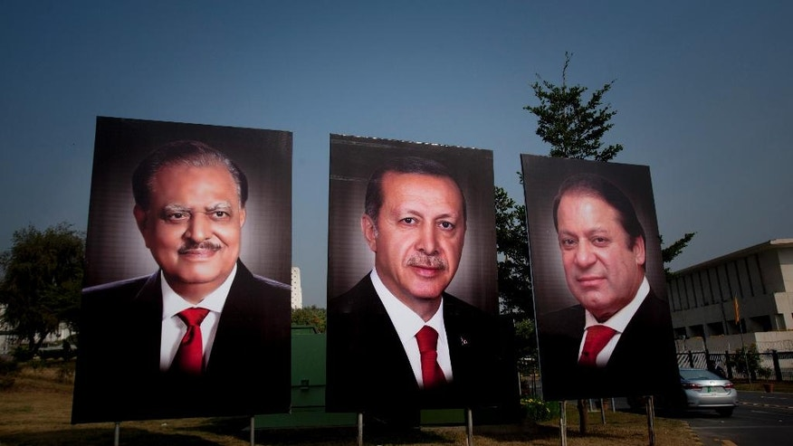 A police officer checks a car at a checkpoint next to billboards showing the portraits of Turkish President Recep Tayyip Erdogan, center, Pakistani President Mamnoon Hussain, left, and Prime Minister Nawaz Sharif, right, welcome Erdogan to Islamabad, Pakistan, Wednesday, Nov. 16, 2016. (AP Photo/Anjum Naveed)