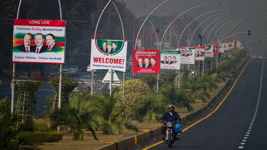 A motorcyclist drives past as billboards showing portraits of Turkish President Recep Tayyip Erdogan, center, Pakistani President Mamnoon Hussain, left, and Prime Minister Nawaz Sharif, right, welcome Erdogan to Islamabad, Pakistan, Wednesday, Nov. 16, 2016. Pakistan has ordered 400 Turk nationals associated with the Pak-Turk International chain of schools and colleges to leave the country in the next 72 hours, says a statement on the school's website. The deportation order comes as Turkish President Erdogan is to arrive in Islamabad on a two-day visit to discuss bilateral, International and regional issues with Pakistani leadership. (AP Photo/Anjum Naveed)