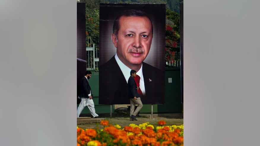 Pakistanis walk pasts billboards showing the portrait of Turkish President Recep Tayyip Erdogan, to welcome Erdogan to Islamabad, Pakistan, Wednesday, Nov. 16, 2016. (AP Photo/Anjum Naveed)