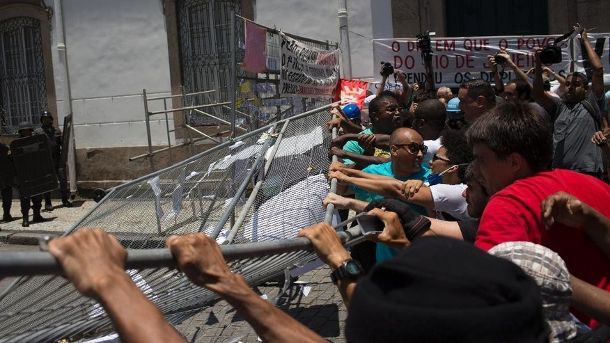Demonstrators tear down a barrier outside the state of Rio de Janeiro's legislative assembly building, where lawmakers are discussing austerity measures in Rio de Janeiro, Brazil, Wednesday, Nov. 16, 2016. The state of Rio de Janeiro is mired in a fiscal crisis, and thousands of state employees have not been paid, or have been paid months late. (AP Photo/Leo Correa)