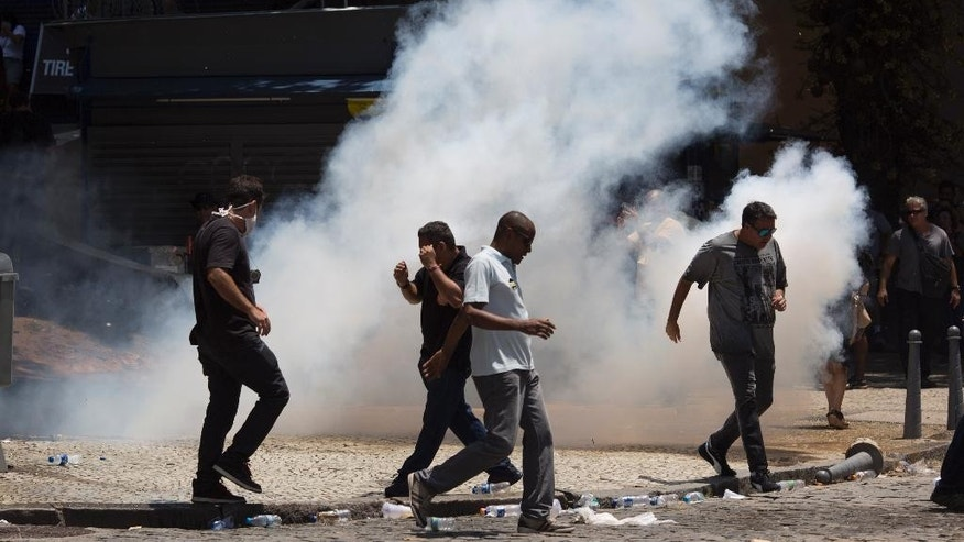 Demonstrators run amid tear gas fired by police outside the state of Rio de Janeiro's legislative assembly building, where lawmakers are discussing austerity measures in Rio de Janeiro, Brazil, Wednesday, Nov. 16, 2016. Brazil is suffering its worst recession in decades while the state of Rio de Janeiro is mired in a fiscal crisis, and thousands of state employees have not been paid or have been paid months late. (AP Photo/Leo Correa)