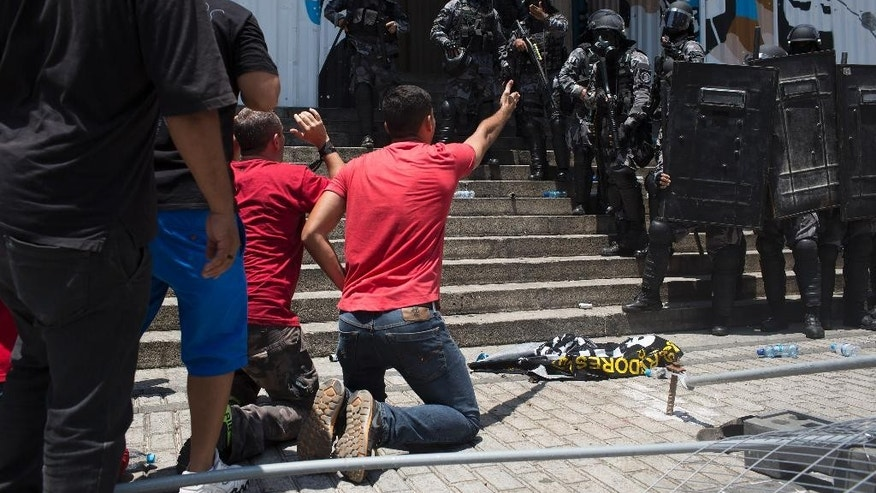 Demonstrators kneel before police outside the state of Rio de Janeiro's legislative assembly building, where lawmakers are discussing austerity measures in Rio de Janeiro, Brazil, Wednesday, Nov. 16, 2016. Brazil is suffering its worst recession in decades while the state of Rio de Janeiro is mired in a fiscal crisis, and thousands of state employees have not been paid or have been paid months late. (AP Photo/Leo Correa)