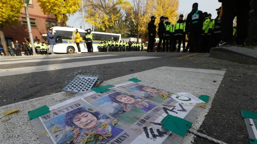 Satirical posters of South Korean President Park Geun-hye are seen on the street near the presidential house in Seoul, South Korea, Wednesday, Nov. 16, 2016. South Korean prosecutors want to question Park this week over suspicion that she let a shadowy longtime confidante manipulate power from behind the scenes, an official said Sunday. (AP Photo/Ahn Young-joon)