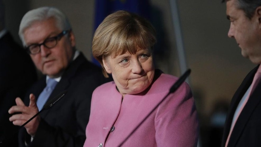 German Chancellor and Chairwomen of the German Christian Democratic Party (CDU), Angela Merkel, center, looks towards Sigmar Gabriel, right, Chairman of the German Social Democratic Party (SPD) during a joint statement in Berlin, Germany, Wednesday, Nov. 16, 2016 on the succession of German President Joachim Gauck. At left is German Foreign Minister Frank-Walter Steinmeier who will run for the German presidency. (AP Photo/Michael Sohn)