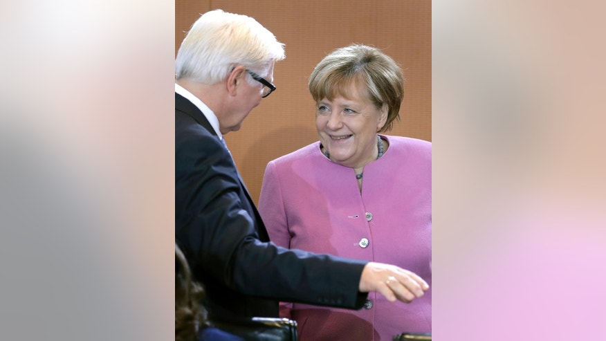 German Chancellor Angela Merkel, right, and German Foreign Minister Frank-Walter Steinmeier, left, talk as they arrive for the weekly cabinet meeting at the Chancellery in Berlin, Germany, Wednesday, Nov. 16, 2016. (AP Photo/Michael Sohn)