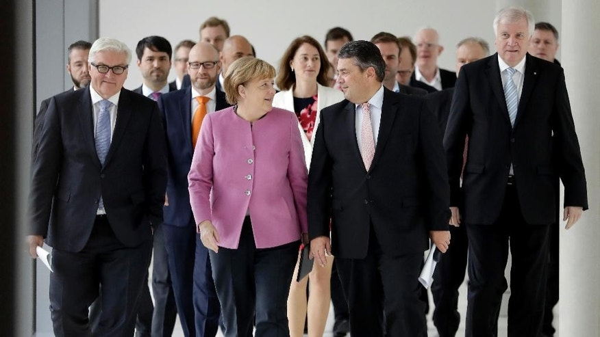 Front from left, German Foreign Minister Frank-Walter Steinmeier, German Chancellor and Chairwomen of the German Christian Democratic Party (CDU), Angela Merkel, the Chairman of the German Social Democratic Party (SPD), Sigmar Gabriel, and the Chairman of the German Christian Social Union, Horst Seehofer, arrive for a joint statement in Berlin, Germany, Wednesday, Nov. 16, 2016 where they announced that Steinmeier will run for the succession of German President Joachim Gauck. (AP Photo/Michael Sohn)