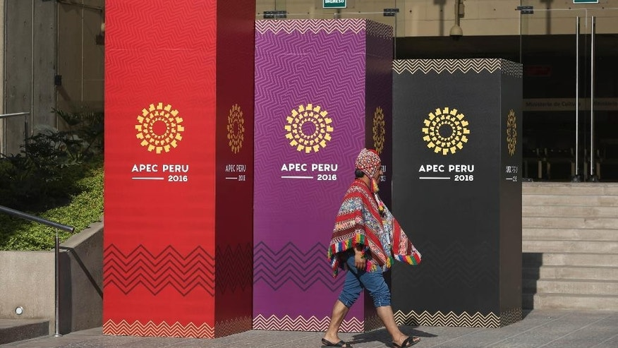 A man dressed in traditional Andean clothes walks past the logo of the APEC 2016 summit in Lima, Peru, Wednesday, Nov. 16, 2016. Lima will host world leaders at this week's Asian-Pacific economic summit. (AP Photo/Martin Mejia)
