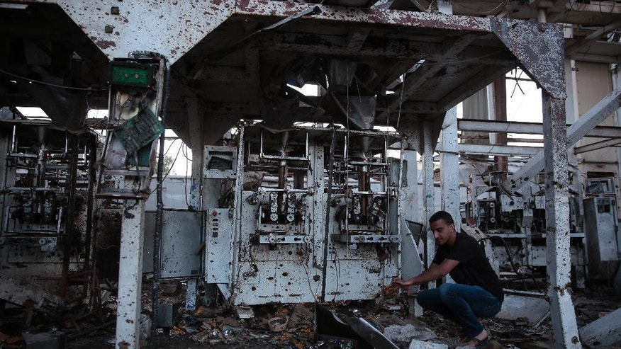 In this Oct. 4, 2016 photo, factory manager, Mustafa Elaghil, inspects a food factory that was hit by Saudi-led airstrikes, in Sanaa, Yemen. In the air campaign by Saudi Arabia and its allies against Yemen's Shiite rebels, rights experts say there has been a pattern by the Saudi-led coalition in depending on faulty intelligence, failing to distinguish between civilian and military targets and disregarding the likelihood of civilian casualties. Experts say some of the strikes likely amount to war crimes. (AP Photo/Hani Mohammed)