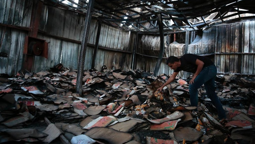 In this, Oct. 4, 2016 photo, factory manager, Mustafa Elaghil, inspects a food factory hit by Saudi-led airstrikes, in Sanaa, Yemen. In the air campaign by Saudi Arabia and its allies against Yemen's Shiite rebels, rights experts say there has been a pattern by the Saudi-led coalition in depending on faulty intelligence, failing to distinguish between civilian and military targets and disregarding the likelihood of civilian casualties. Experts say some of the strikes likely amount to war crimes. (AP Photo/Hani Mohammed)