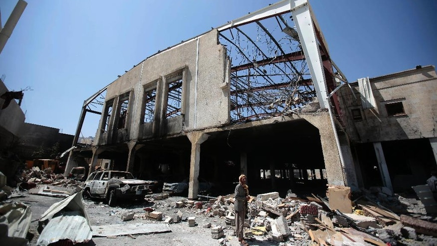 In this Oct. 13, 2016 photo, a Yemeni man stands in front of a funeral hall, destroyed by a deadly Saudi-led airstrike on Saturday, Oct. 8, 2016, in Sanaa, Yemen. In the air campaign by Saudi Arabia and its allies against Yemen's Shiite rebels, rights experts say there has been a pattern by the Saudi-led coalition in depending on faulty intelligence, failing to distinguish between civilian and military targets and disregarding the likelihood of civilian casualties. Experts say some of the strikes likely amount to war crimes. (AP Photo/Hani Mohammed)
