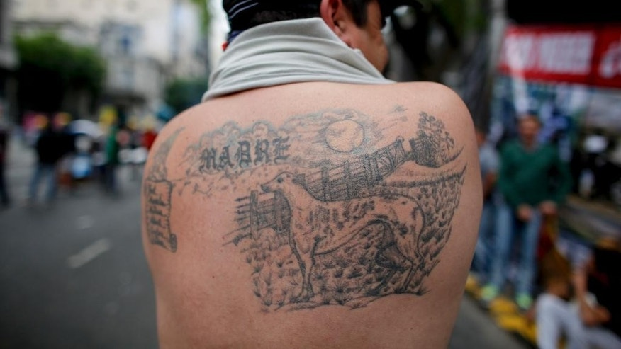 A supporter of greyhound racing shows off a tattoo of his dog outside Congress in Buenos Aires, Argentina, Wednesday, Nov. 16, 2016. Lawmakers are expected to vote Wednesday on a law that would prohibit greyhound racing nationwide. (AP Photo/Victor R. Caivano)