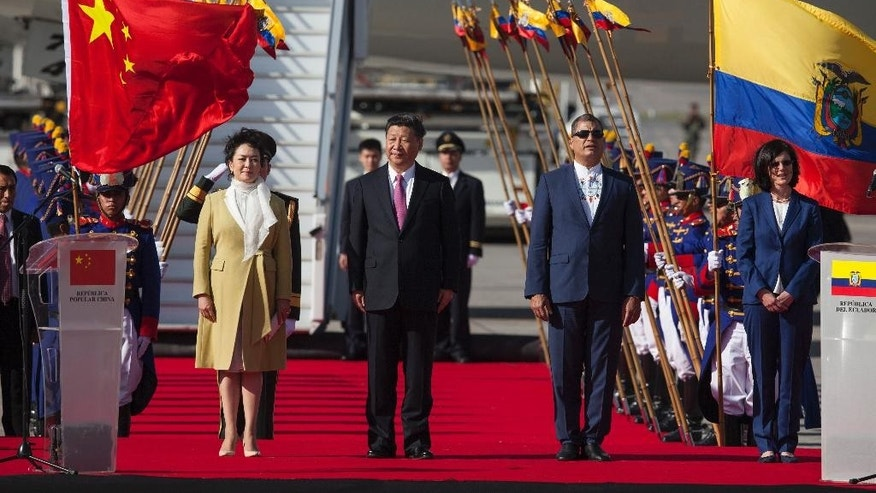China's President Xi Jinping, center, and his wife Peng Liyuan stand with Ecuador's President Rafael Correa, second from right, during a welcoming ceremony at Mariscal Sucre Airport in Quito, Ecuador, Thursday, Nov. 17, 2016. Xi Jinping is in Ecuador for two days before heading to Peru for the APEC summit. (AP Photo/Ana Buitron)