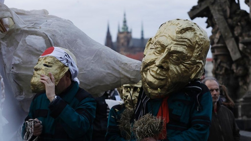 A man  wearing a mask depicting Czech Republic's President Milos Zeman, right, marches across the medieval Charles Bridge as part of commemorations for the 27th anniversary of the so called Velvet Revolution in Prague, Czech Republic, Thursday, Nov. 17, 2016. (AP Photo/Petr David Josek)
