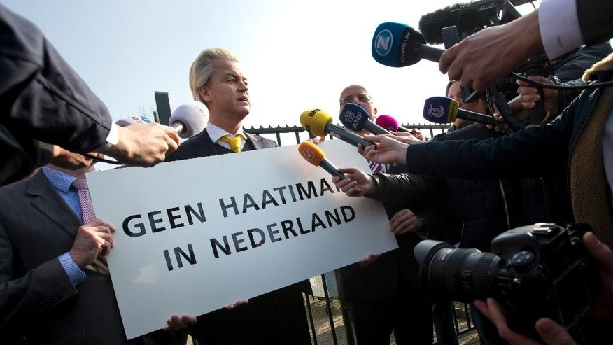 "FILE - In this Thursday, April 9, 2015 file photo Geert Wilders, leader of the anti-Islam Freedom Party, holds a sign reading ""No Hate Imams in the Netherlands"" in Utrecht, central Netherlands. Dutch prosecutors have begun summing up their case against populist anti-Islam lawmaker Geert Wilders in his hate-speech trial that pits freedom of expression against the Netherlands' anti-discrimination laws. (AP Photo/Peter Dejong, File)"
