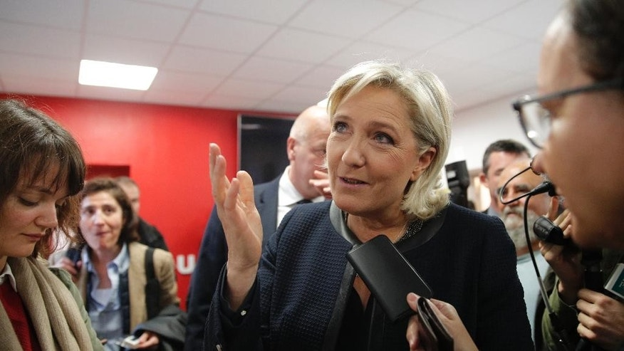 Far-right leader Marine le Pen answers reporters as she inaugurates her campaign headquarters, Wednesday, Nov.16, 2016 in Paris. Le Pen is convinced that her anti-immigration, anti-Islam views can lead her to the presidency in five months. (AP Photo/Christophe Ena)