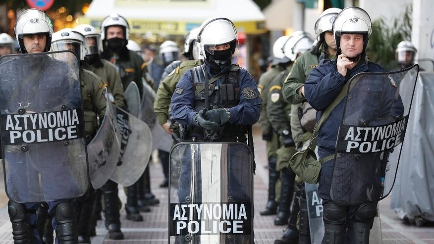 Greek riot police officers keep a watchful eye at demonstrators in a march in central Athens, Thursday, Nov. 17, 2016. Several thousand people march to the U.S. Embassy in Athens under tight police security to commemorate a 1973 student uprising that was crushed by Greece's military junta, that ruled the country from 1967-74. (AP Photo/Thanassis Stavrakis)