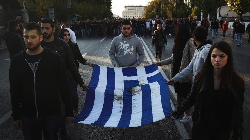 University students hold a blood-stained Greek flag from the deadly 1973 student uprising in Athens, Thursday, Nov. 17, 2016. Several thousand people marched to the U.S. Embassy in Athens under tight police security to commemorate a 1973 student uprising that was crushed by Greece's military junta, that ruled the country from 1967-74. (AP Photo/Yorgos Karahalis)