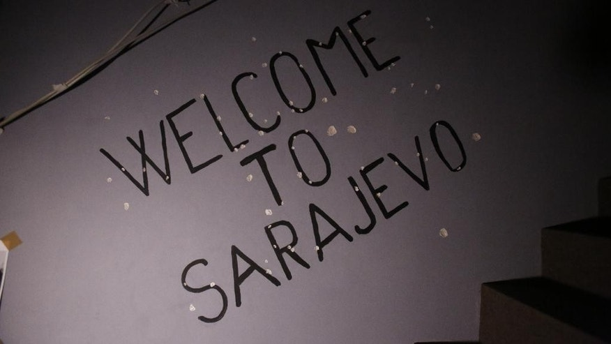 "In this Nov. 12, 2016 photo, ""Welcome to Sarajevo"" graffiti is seen on a bullet-raked wall of the War Hostel in Sarajevo that offers visitors a unique opportunity to live like civilians in a war zone. Hostel guests must do without electricity, running water and heating, but have the luxury of knowing they won't be killed, starved or lose family or friends. (AP Photo/Amel Emric)"