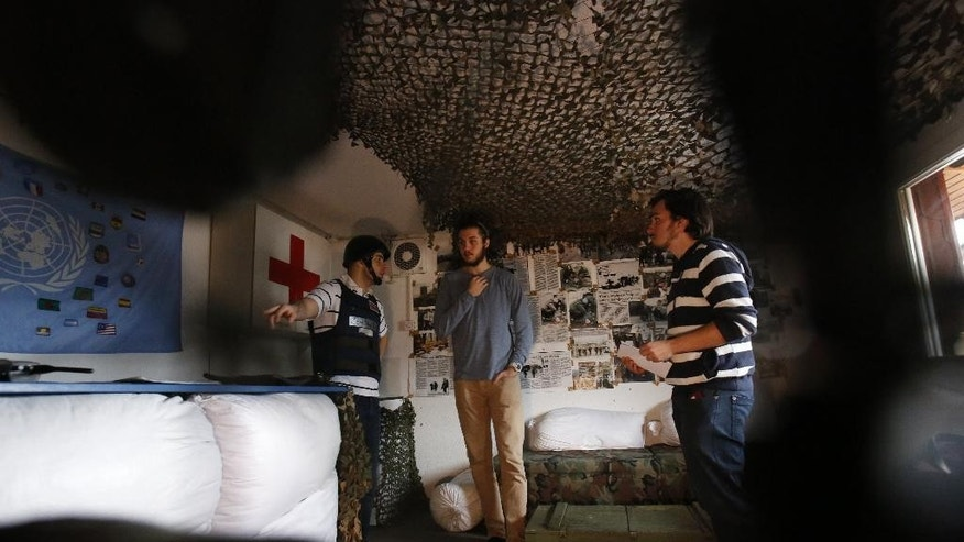 In this Nov. 12, 2016 photo, Bosnian Arian Kurbasic, left, the owner of the War Hostel in Sarajevo, talks with his guests, Andrew Burns from the U.S., center, and Eren Bastaymaz from Turkey in the hostel's common room. The War Hostel offers visitors a unique opportunity to live like civilians in a war zone, but with the luxury of knowing they won't be killed, starved or lose family or friends. (AP Photo/Amel Emric)