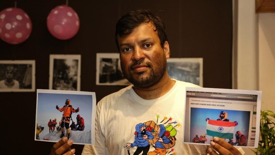 FILE- In this July 4, 2016 file photo, Indian climber, Satyarup Sidhantha holds on his right hand a photograph that shows him on Mount Everest, along with what he says is an altered version of the same used by an Indian couple to make it appear they were on the summit, as he displays them for the Associated Press in Kolkata, India.Two police officers — a husband and wife — have been suspended in India for falsely claiming they scaled Mount Everest in Nepal in May, police said Thursday. Nepal's government earlier canceled the climbing certificates issued to Dinesh Rathod and Tarkeshwari Rathod after it found they had presented a fake photograph of themselves on Everest's summit. (AP Photo/ Bikas Das, File)