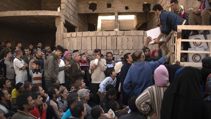 Residents gather to receive food supplies being distributed in an area previously held by Islamic State militants and now controlled by Iraqi forces in Mosul, Iraq, Thursday, Nov. 17, 2016. (AP Photo/Felipe Dana)