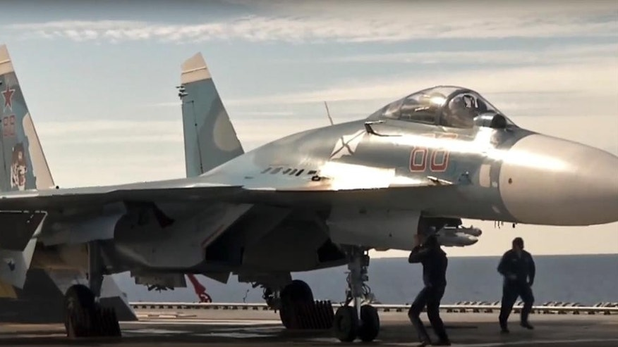 In this photo made from the footage taken from Russian Defense Ministry official web site on Tuesday, Nov. 15, 2016, a Russian Su-33 fighter jet stands on the flight deck of the Admiral Kuznetsov aircraft carrier in the eastern Mediterranean Sea. The Russian military on Tuesday launched a series of strikes on militant targets in Syria involving carrier-borne fighters, marking the Admiral Kuznetsov's combat debut. (Russian Defense Ministry Press Service/ Photo via AP)